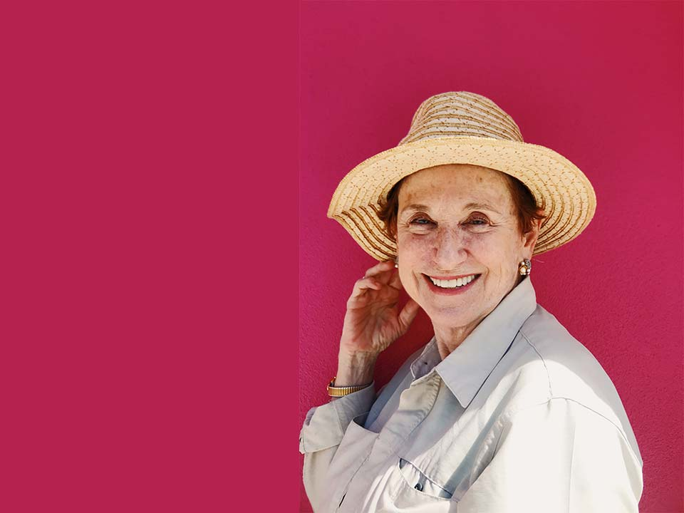Old lady wearing a hat on a pink background