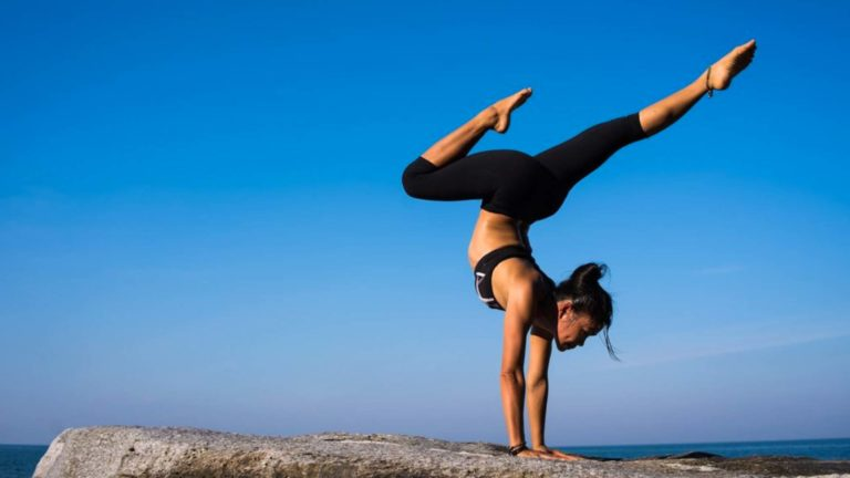 girl performing yoga on a rock by the sea